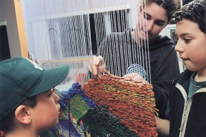"""Collective Project in a School"", photo: Jamie Cruickshank. We set up so that weaving can be done on both the front and back sides of the loom during a collective project in a school, in order to facilitate participation of all the students in the school."