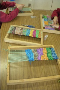 """Children Working in Pairs"", photo: Moon Rain Centre. In Moon Rain Centre's artist-in-the-schools projects, the children work in pairs, helping each other to warp their individual frame looms, keep the tension and tie the knots."